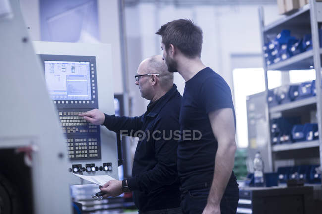 Two men operating machine in a factory — Stock Photo