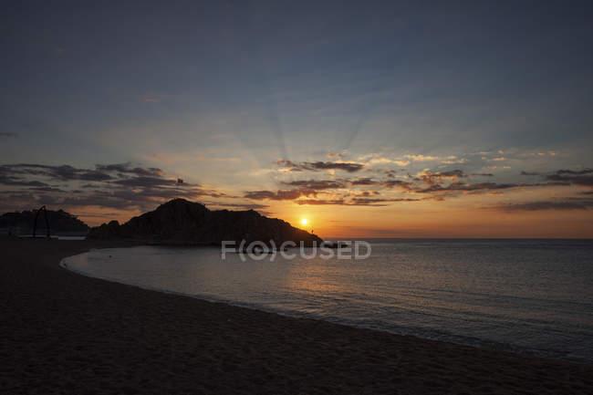 Spain, Costa Brava, Blanes town, sunrise at Mediterranean Sea, SAbanell beach and Sa Palomera rock — Stock Photo