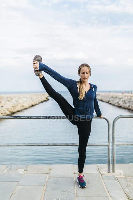 Молодая женщина, занимающаяся йогой позирует на пляже — стоковое фото