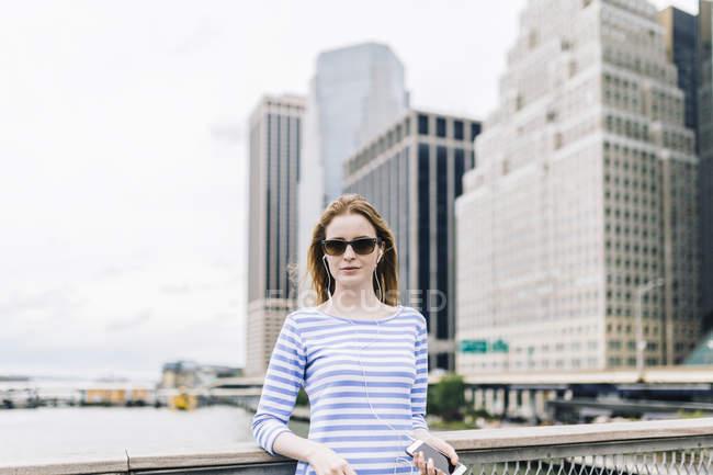 Mujer joven parada en Manhattan en la barandilla, sosteniendo el teléfono inteligente - foto de stock