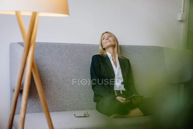 Розслабленої підприємець, сидячи на дивані — стокове фото