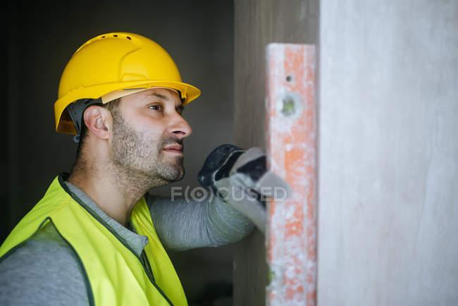 Портрет работника, с помощью уровня на стене — стоковое фото