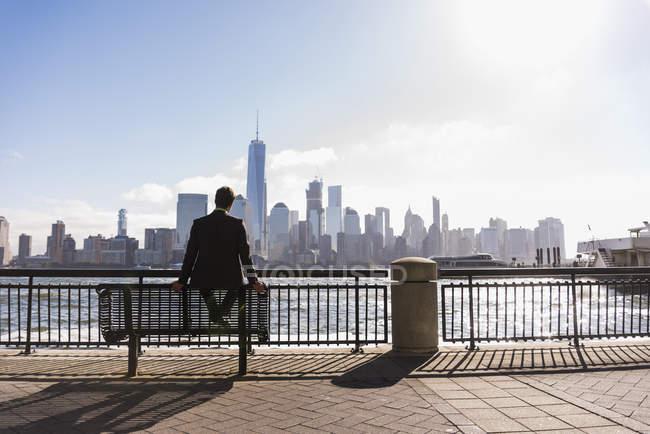 Homme assis sur un banc au bord de l'eau du New Jersey avec vue sur Manhattan, États-Unis — Photo de stock