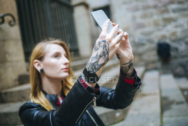 Tattooed woman taking a selfie with a smart phone — Stock Photo