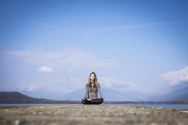 Femme pratiquant le yoga sur une jetée au bord d'un lac — Photo de stock