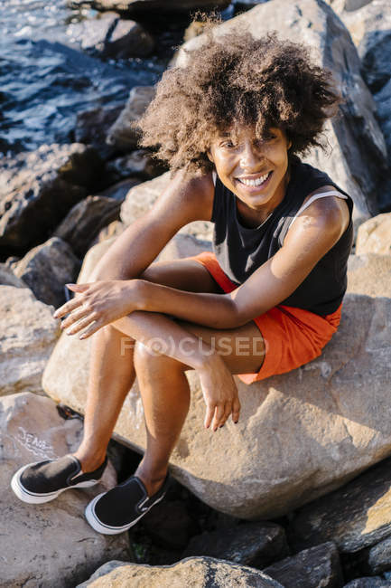 Portrait of young woman sitting on rocky river shore — Stock Photo