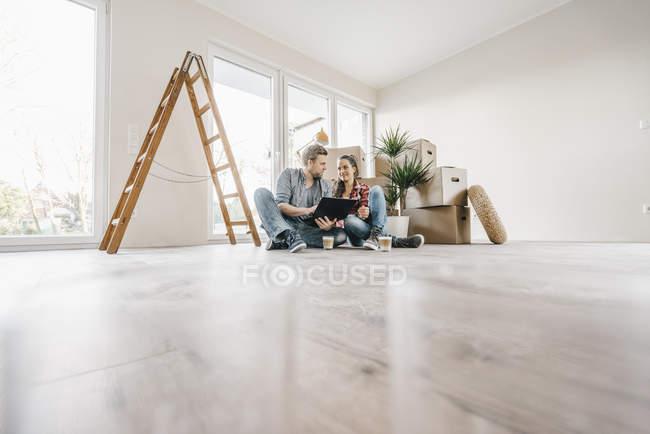 Pareja sentada en el piso de nuevo hogar entre cajas de mudanza - foto de stock