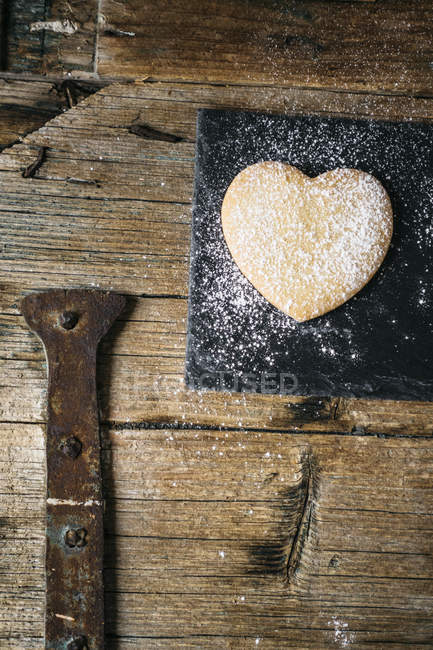 Homemade heart-shaped cookie on slate on wooden surface — Stock Photo