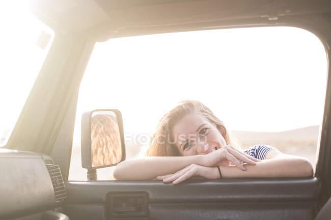 Giovane donna appoggiata al finestrino dell'auto e guardando dentro — Foto stock