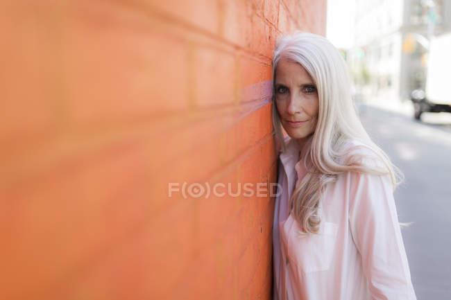 Ritratto di donna anziana in piedi vicino al muro arancione — Foto stock
