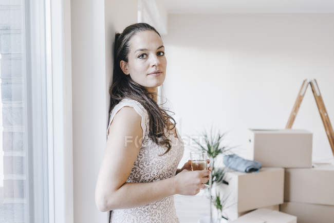 Mature businesswoman standing with glass of water in new home — Stock Photo