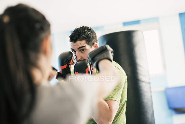 Sporty caucasian man abd woman boxing in gym — Stock Photo