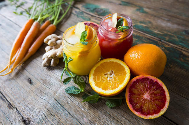 Closeup view of sliced citrus fruits with juice and carrots — Stock Photo