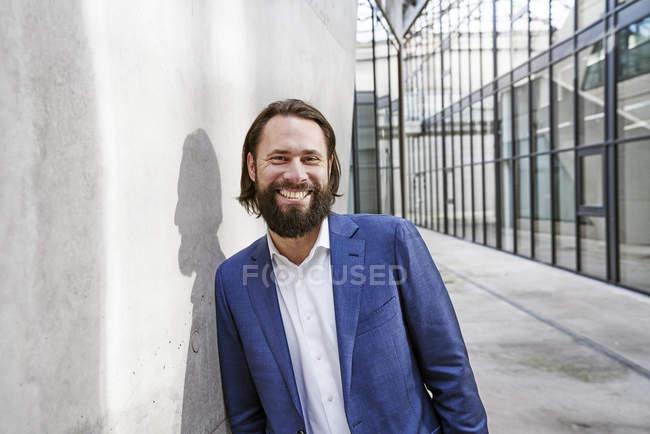 Portrait d'homme d'affaires heureux appuyé contre un mur — Photo de stock