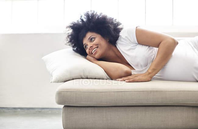 Donna incinta rilassante sul divano e guardando lateralmente — Foto stock