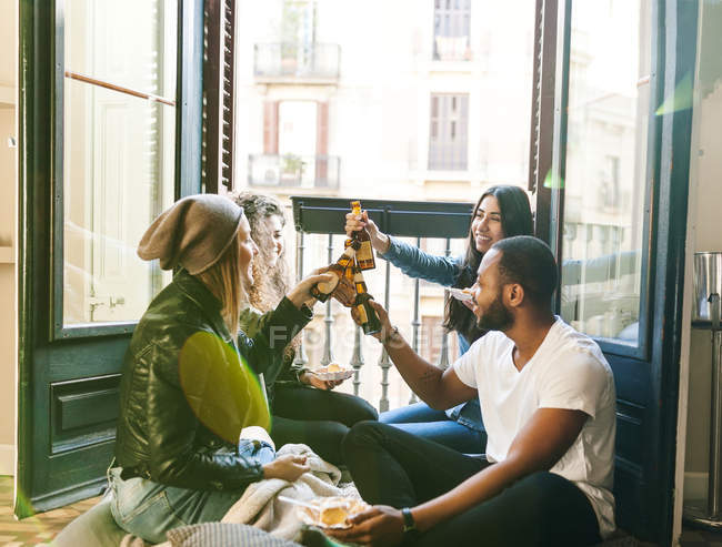 Portrait of young friends toasting with beer — Stock Photo