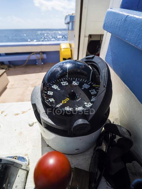 Primo piano della bussola su una nave di navigazione con mare su priorità bassa — Foto stock