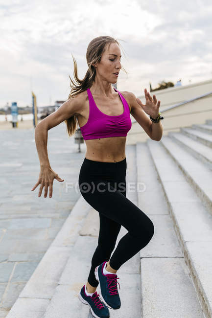Young sporty woman running upstairs — Stock Photo