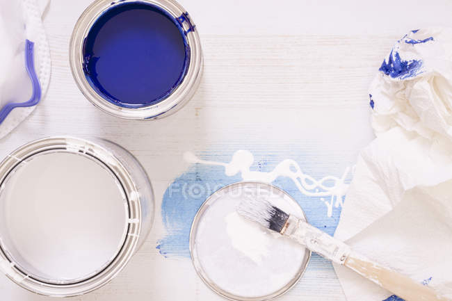 Used paint brush and paint tins with blue and white varnish — Stock Photo