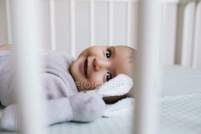 Happy baby girl lying on crib with stuffed rabbit — Stock Photo