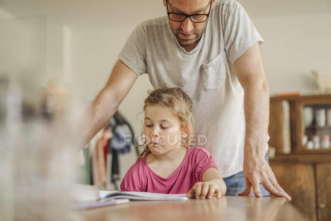 Отец проверяет домашнюю работу дочери дома — стоковое фото
