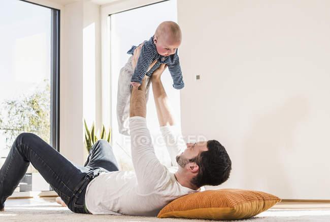 Батько, граючи з дитину сина, лежачи на килимі вдома — стокове фото