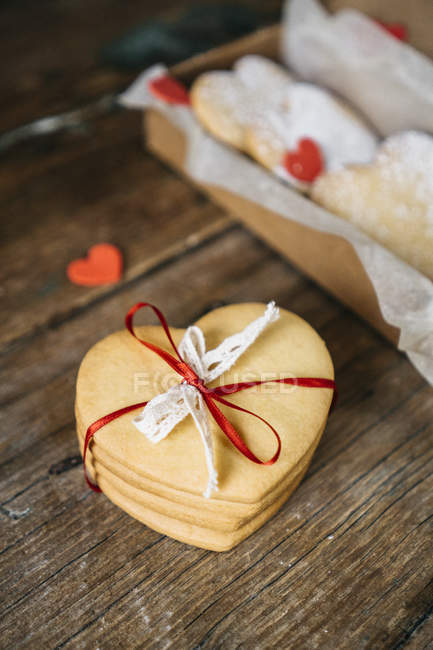 Stacked home-baked heart-shaped cookies tied with ribbon as gift on wood — Stock Photo