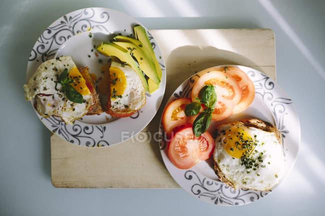 Вид зверху яєчня з нарізані помідори і авокадо — стокове фото