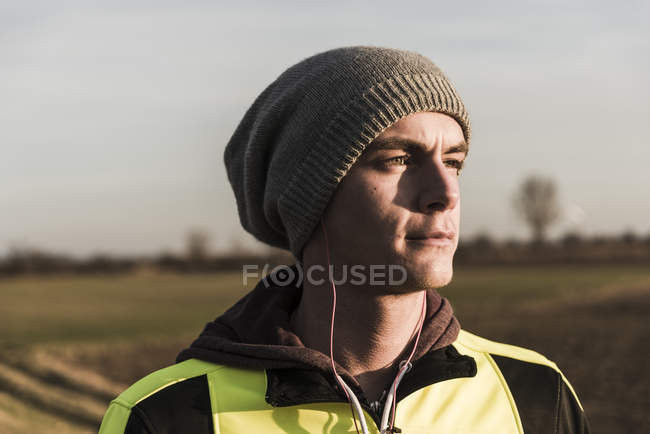 Portrait of young man with earbuds in field — Stock Photo