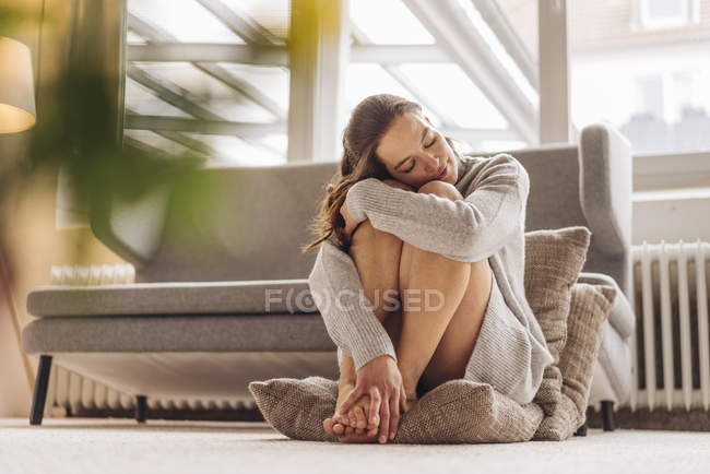 Woman with closed eyes sitting on cushion on floor — Stock Photo