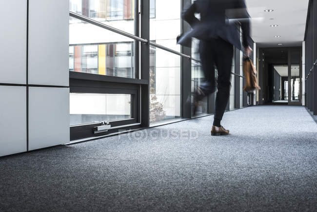 Cropped portrait of businessman running in corridor — Stock Photo
