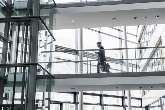 Портрет молодого бизнесмена, использующего смартфон в коридоре — стоковое фото