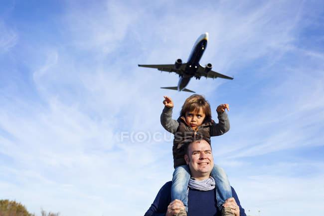 Портрет людина холдингу хлопчик на плечах з літака вище — стокове фото