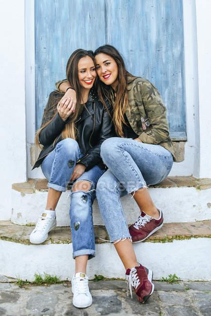 Deux jeunes femmes souriantes assises devant la porte bleue — Photo de stock