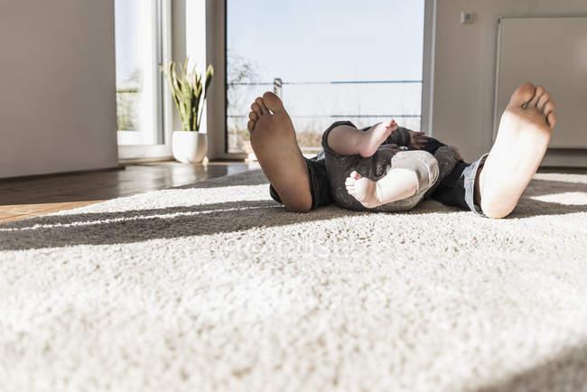 Босими ногами Син батька та дитини, лежачи на килимі вдома — стокове фото