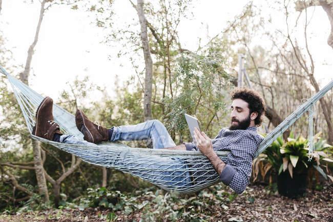 Человек лежит на гамаке с цифровой таблеткой — стоковое фото