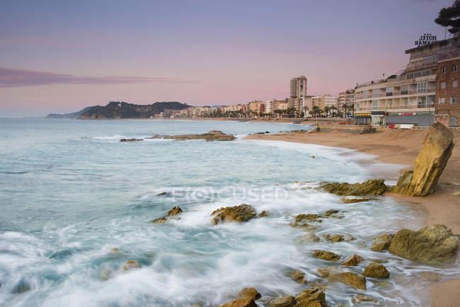 Spain, Costa Brava, Lloret de Mar,  beach with rocks at sunrise — Stock Photo