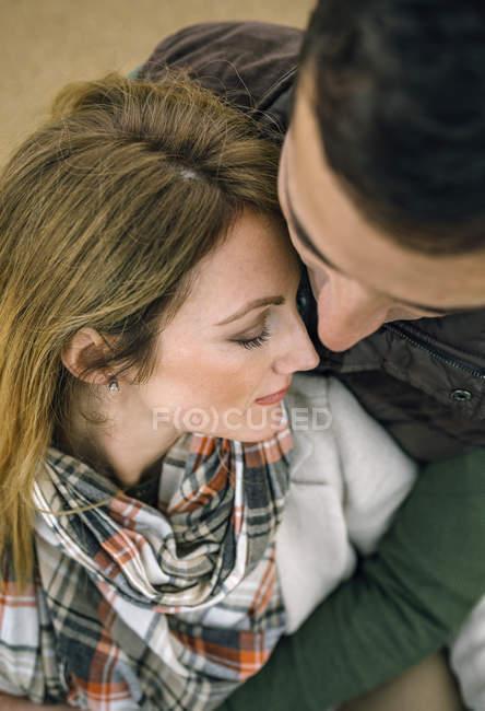 Fechar-se de homem abraçando a mulher com os olhos fechados. Vista de cima . — Fotografia de Stock