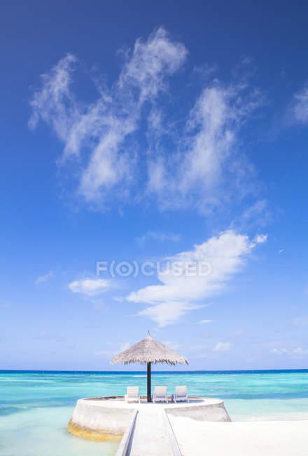 Maledives, Південний Мале Атолл, шезлонгами під парасольку на піщаному пляжі — стокове фото