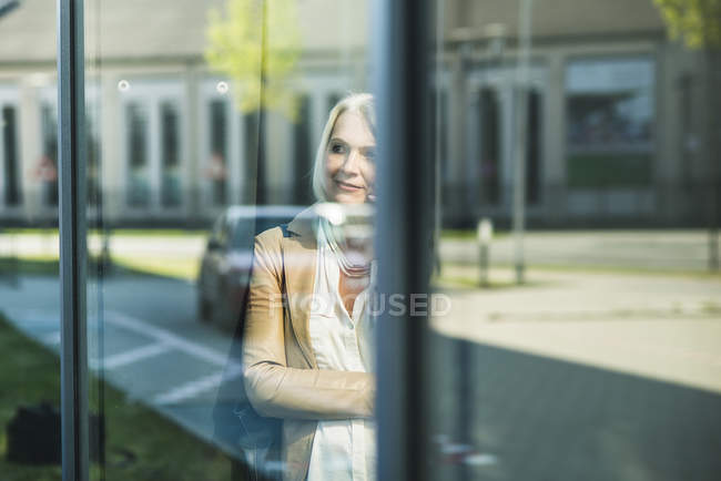 Mature woman looking at mirrored self at window pane — Stock Photo