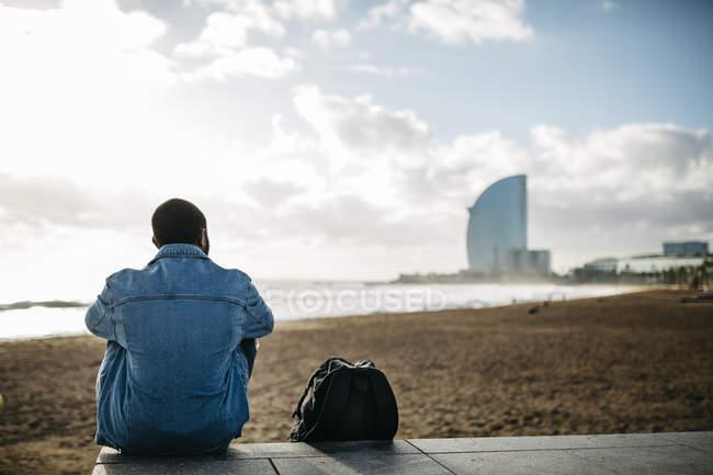 Іспанія, Барселона. Молодий мандрівник, сидячи біля моря — стокове фото