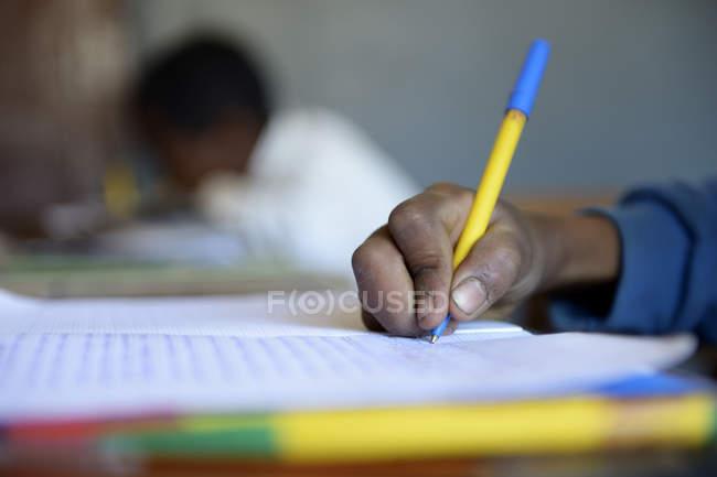 Gros plan d'écolier écrire dans le cahier à l'école primaire — Photo de stock