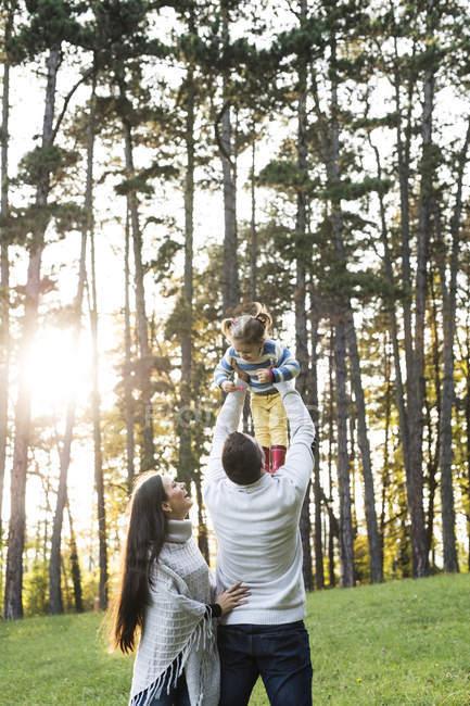 Pais felizes brincalhões com menina na floresta — Fotografia de Stock