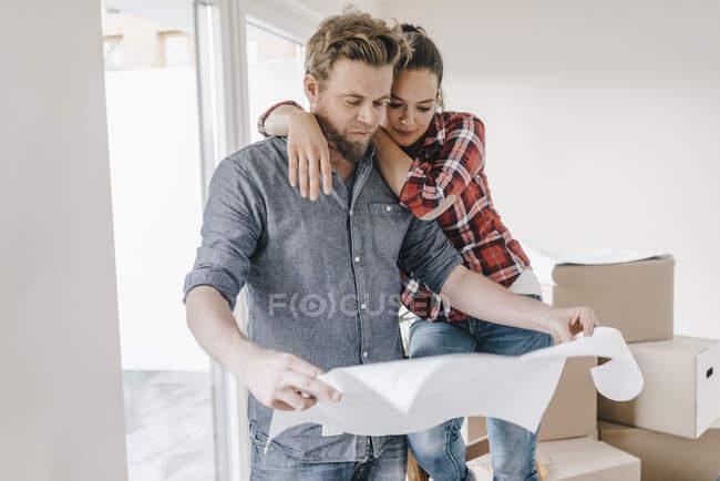 Pareja en el plano del nuevo hogar - foto de stock