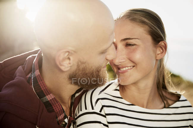 Young couple in love kissing at backlit in nature — Stock Photo