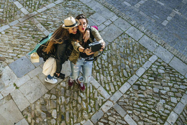 Young friends taking a selfie with a camera on street — Stock Photo