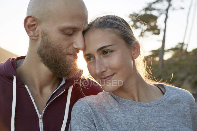 Relaxed young couple in love standing at backlit — Stock Photo