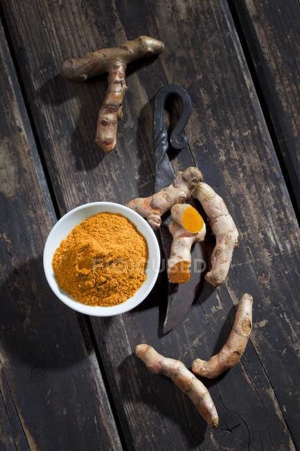 Draufsicht der Kurkuma-Pulver mit Wurzeln und geschmiedete Messer — Stockfoto