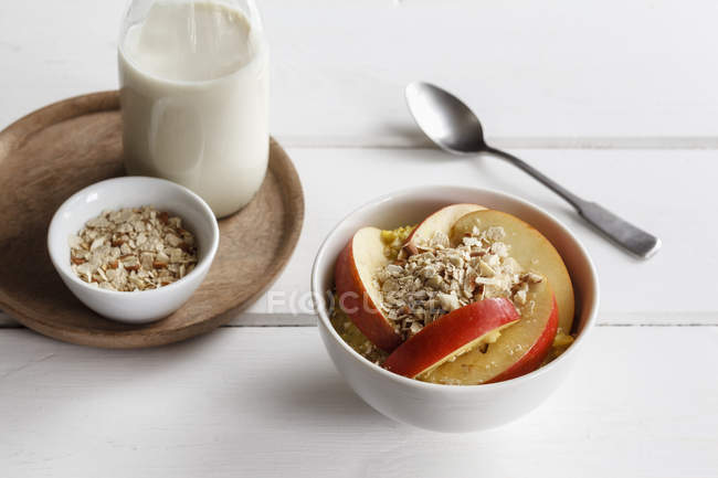 Closeup view of oat flakes with sliced apple and milk in bowls — Stock Photo
