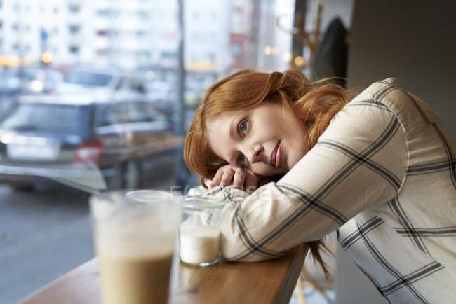 Jovem mulher, sentados em um café a sonhar acordada — Fotografia de Stock